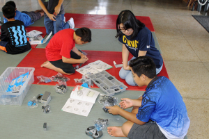 HawCC student Tayeh Madjeska leads Keaukaha students through the instruction manuals of a VEX IQ robotics kit.
